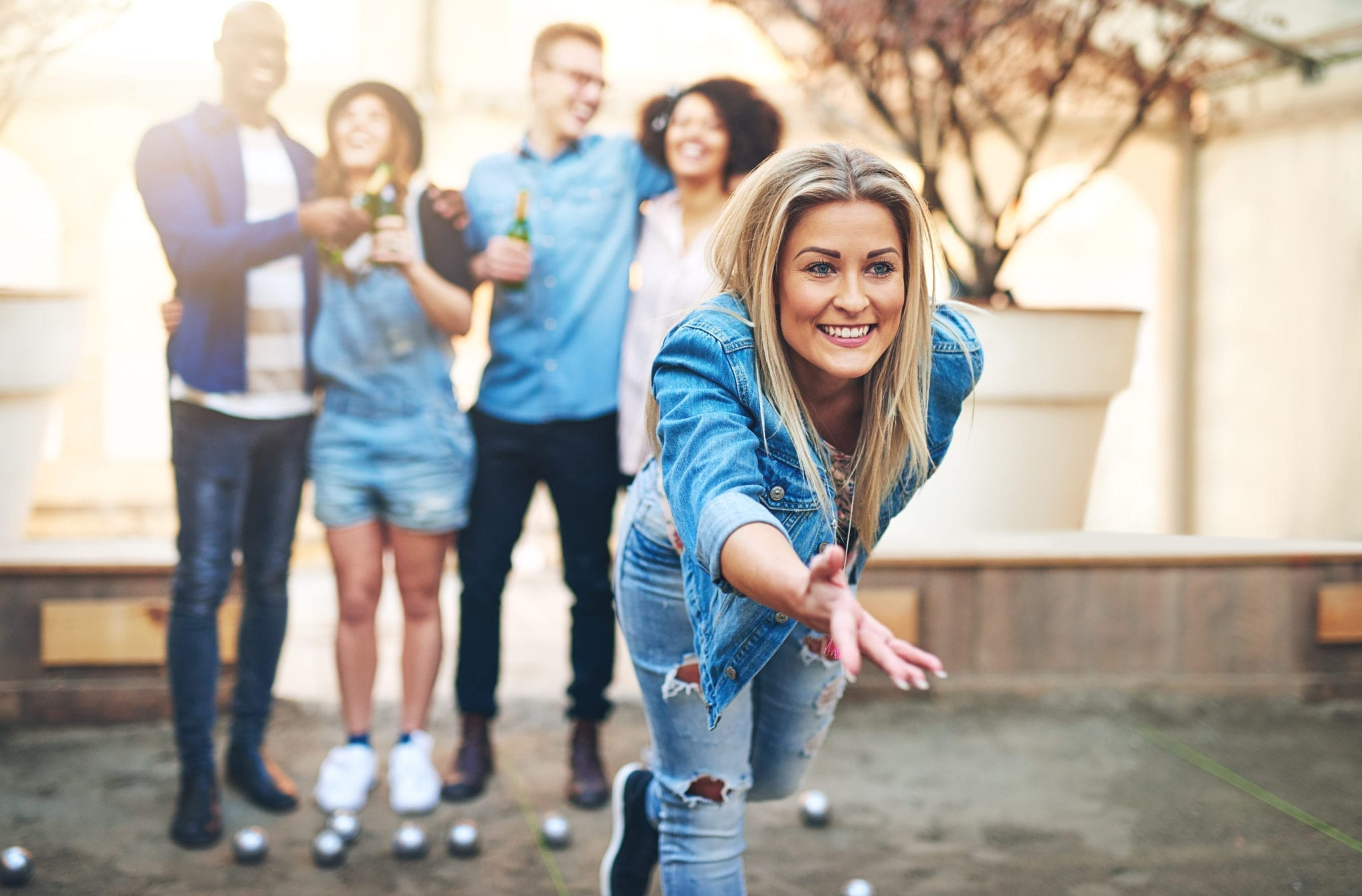 Group of multiracial friends clinking bottles of beer while pretty young woman throwing ball playing petanque.