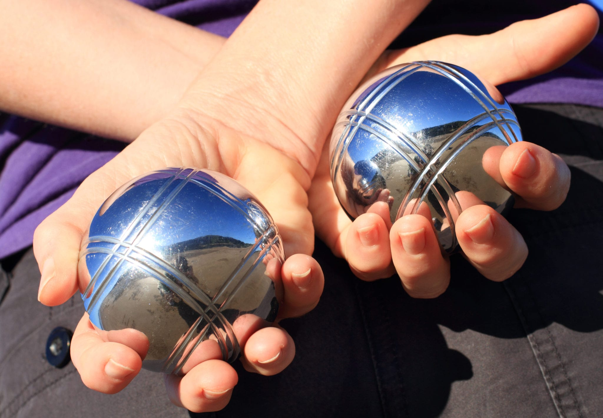 A woman holding two chrome boules behind her back.